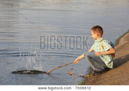 little boy with backpack near pond. he is wallop water. splash.