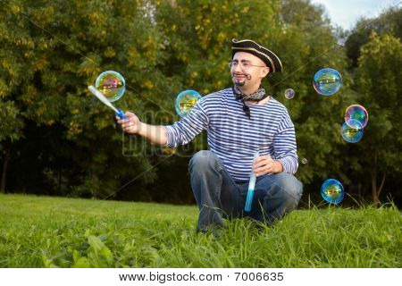 joyful man in pirate suit is sitting on grass and blowing soap bubbles.