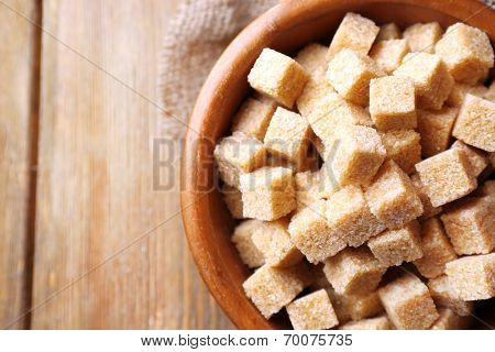 Brown sugar cubes and crystal sugar in bowl on wooden background