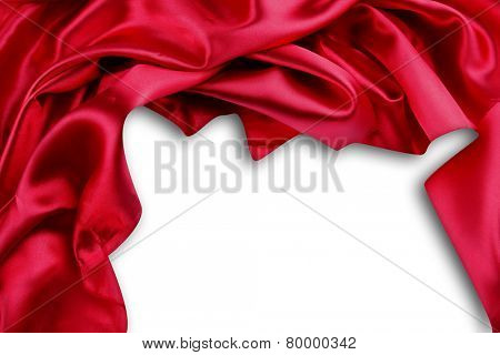 Closeup of folds in red silk fabric on plain background. Advertising copy space
