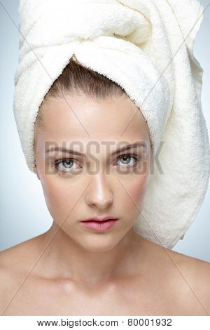 Closeup portrait of young beautiful girl with perfect skin and towel on head