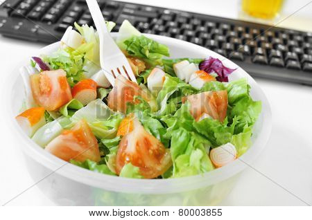 closeup of a salad in a plastic container on the desk of an office
