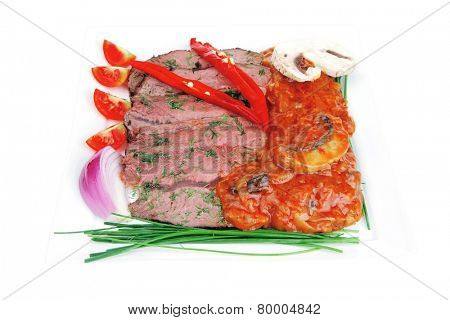 beef on plate with vegetables over white