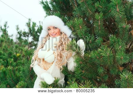 Smiling woman with fur white hat, woolen mittens, sweaters in the winter fir forest. Fir branches.