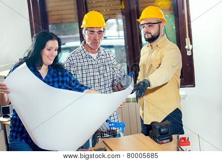 Construction worker and couple looking at the plan, selective focus