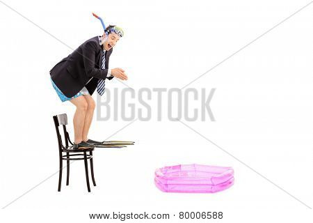 Young businessman ready to jump into a baby pool isolated on white background