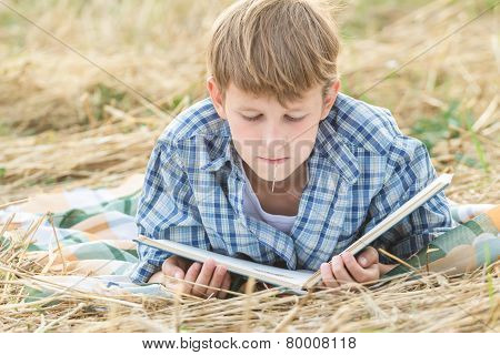 Teenage boy lying with book