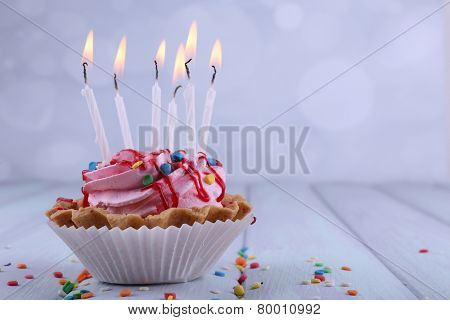 Birthday cup cake with candles and sparkles on color wooden table and light background