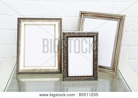 Photo frames on coffee table on brick wall background