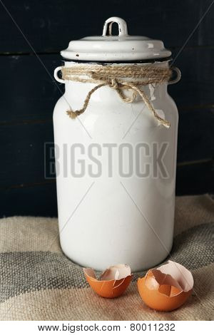 Milk can with eggshell on color wooden background