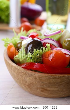 Greek salad in bow on wooden table background
