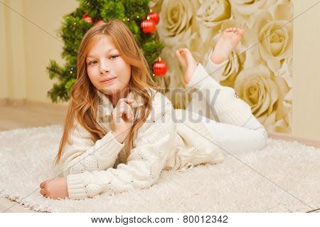 Girl lying on the carpet, looking at the camera and smiling.