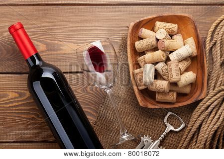 Red wine bottle, glass of wine, bowl with corks and corkscrew. View from above over rustic wooden table background