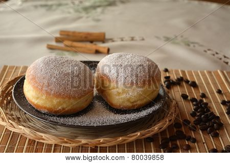 Donuts with powdered sugar on the brown plate on the table