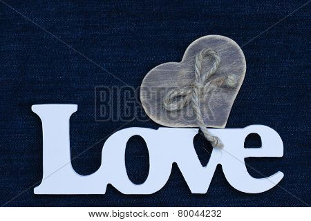 Love text with wooden heart on blue denim