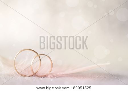 Two Golden Wedding Rings and  Feather - light soft background for marriage