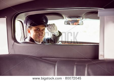 Limousine driver smiling at camera through partition in limousine