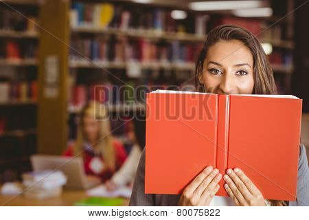 Pretty brunette student holding book in front of her face in library