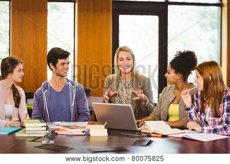 Smiling students and teacher in library at the university