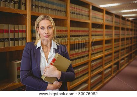 Female librarian posing and holding a book in library