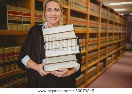 Smiling lawyer holding heavy pile of books standing in library