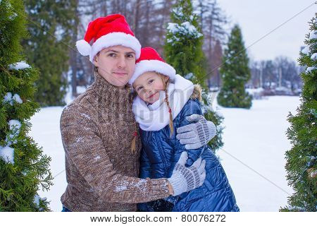 Happy family in Santa hats with christmas tree outdoor