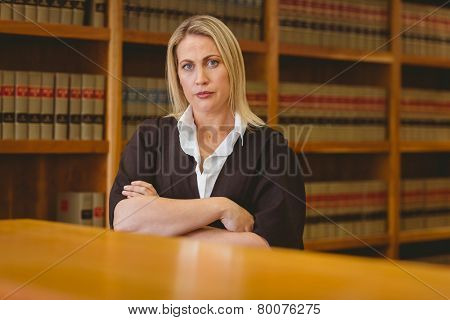 Serious lawyer looking at camera with arms crossed in library