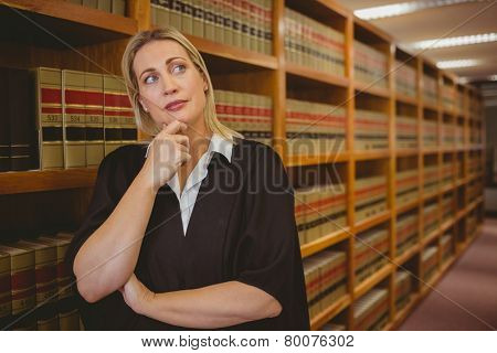 Serious lawyer thinking with hand on chin in library