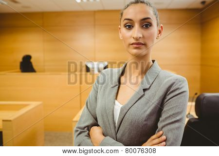 Unsmiling lawyer looking at camera crossed arms in the court room