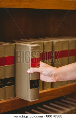 Hand taking a book from bookshelf in the library