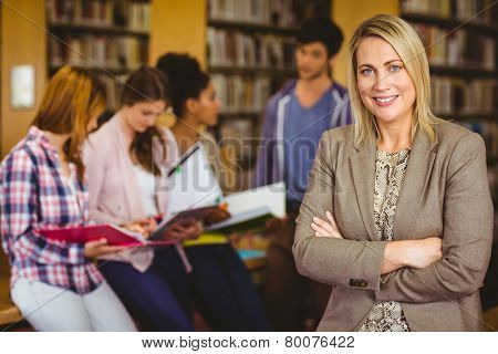 Professor looking at camera with arms folded in library