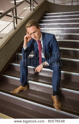 Stressed businessman sitting on steps in office building