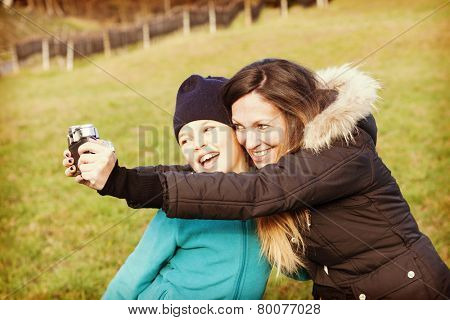 woman and child shooting a selfie with phone