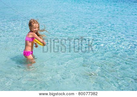 Little girl playing during tropical vacation in the sea