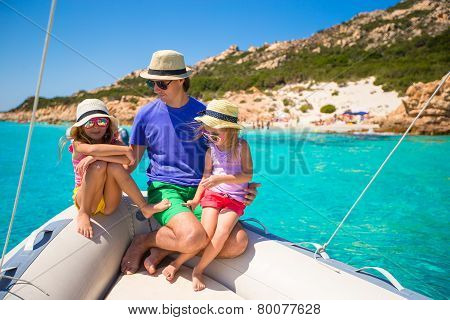 Little girls resting on big boat with happy dad