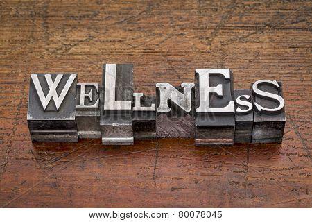 wellness word in mixed vintage metal type printing blocks over grunge wood