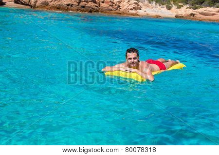 Happy man relaxing on inflatable mattress in clear sea