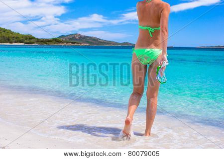 Back view of young girl with snorkeling mask on tropical beach