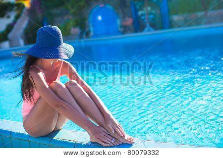 Beautiful young girl relaxing near the swimming pool