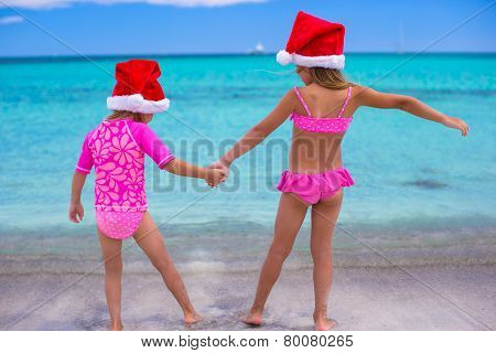 Little girls in Santa hats during summer vacation
