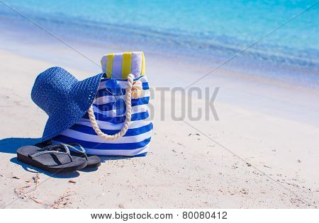 Straw hat, bag and towel on white tropical beach