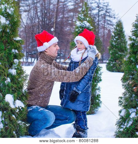 Happy family in Santa hats with christmas tree outdoor