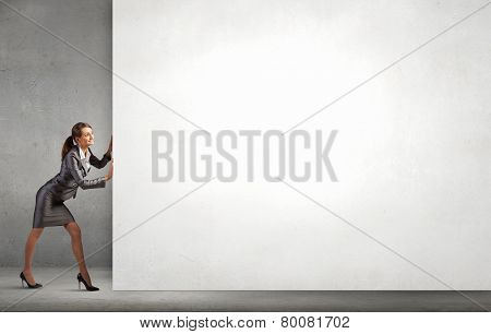 Attractive businesswoman pushing white blank wall. Place for text