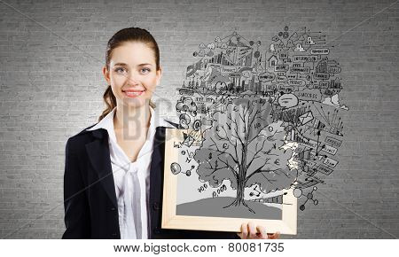 Young businesswoman holding wooden frame with business sketches