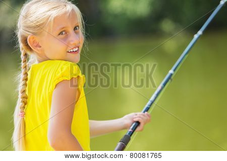 Portrait of cute girl sitting at bank and fishing
