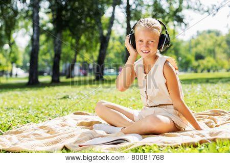 Little cute girl in summer park on blanket wearing headphones