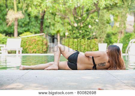 Asia Beautiful Woman In Bikini Lying On Edge Of The Pool