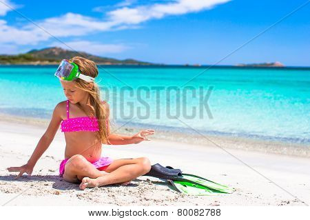 Little girl with flippers and goggles for snorkling on white beach
