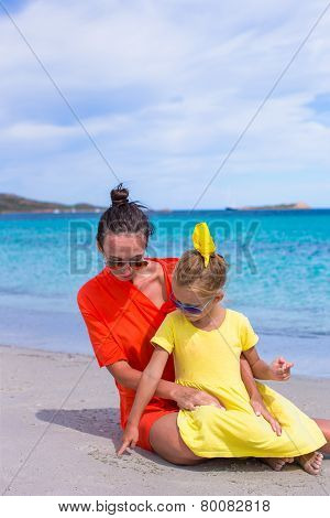 Little girl and happy mom during tropical beach vacation