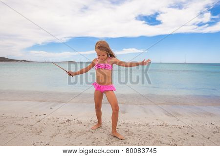 Adorable little girl enjoying tropical beach vacation